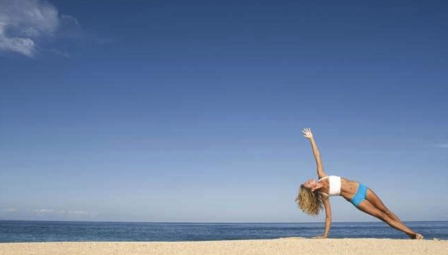 Woman_on_beach_in_yoga_side_plank_pose_LOP08009